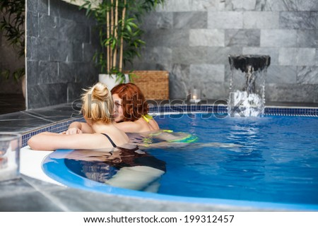 Women relaxing in wellness and spa swimming pool. - stock photo