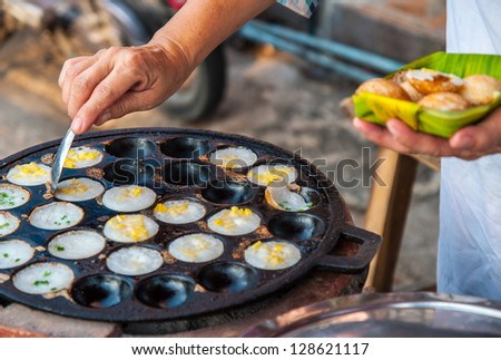Women remove the kanom krok with a rounded spoon , Kind of Thai sweetmeat fried dessert. - stock photo