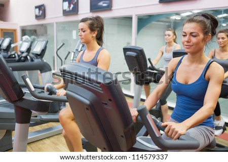 Women riding on  exercise bikes in spinning class in gym - stock photo