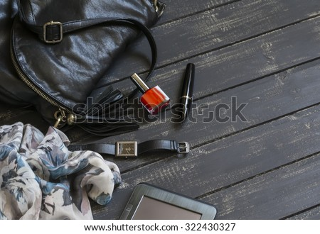 women's accessories black leather handbag, scarf, watch, nail Polish, mascara and tablet computer on a dark wooden surface - stock photo