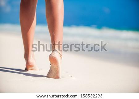 Women's beautiful smooth legs on white sand beach - stock photo
