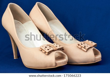 women's  beige leather   peep-toe shoes with bow on a blue  background - stock photo