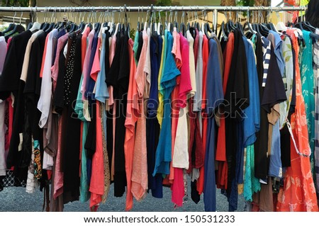 Women's casual summer clothes for sale at street market. - stock photo
