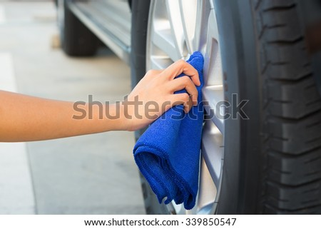 Women's hand wiping on alloy Wheels. - stock photo