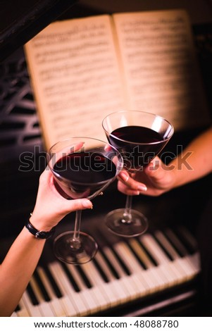 Women's hands holding red wine glasses over piano. - stock photo