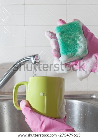 Women's hands wash the cup in the kitchen sink with soapy sponge. - stock photo
