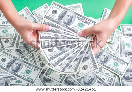 women's hands with a fan out of money - stock photo