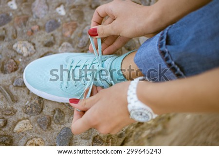 Women's hands with a red manicure knotted laces on sports shoes. The foot stands on the border of sea stones. Walk along the coast in the summer. On the hand put on white watch. - stock photo
