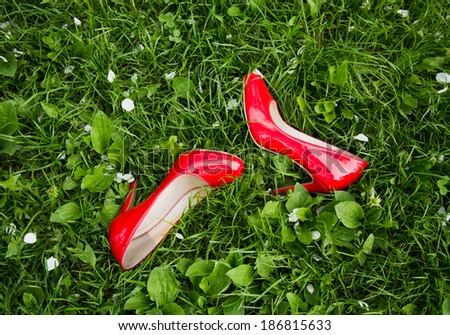 women's red shoes on green grass summer - stock photo
