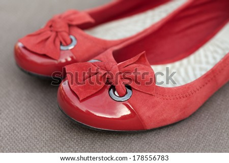 Women's red shoes with bows against a brown material background. - stock photo