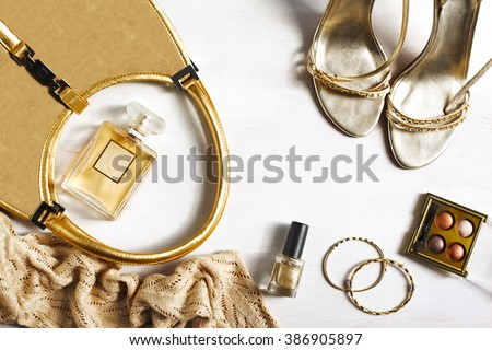 Women's set of fashion accessories in golden color on wooden background: shoes, handbag, perfume and cosmetics - stock photo
