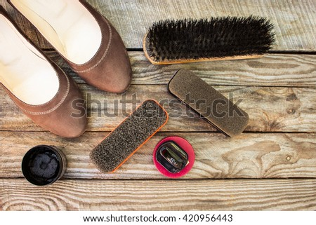 Women's shoes and care products for footwear on wooden background. - stock photo