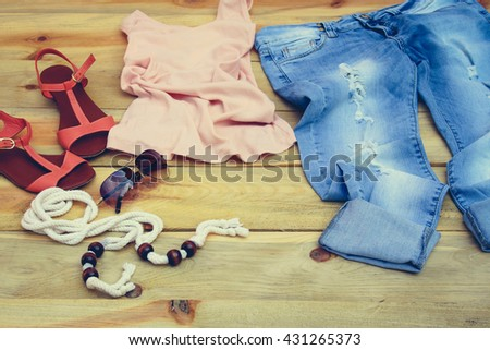 Women's summer clothing and accessories: tank top, jeans, sunglasses, belt, shoes on wooden background.Toned image. - stock photo