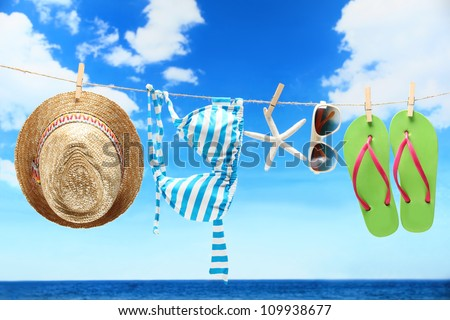 Women's swimsuit, hat and flip-flops hanging on a rope near beach. - stock photo