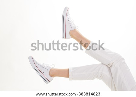 Women's white gumshoes. White trousers and casual footwear. Warm season style for women. Practical fabric shoes. - stock photo
