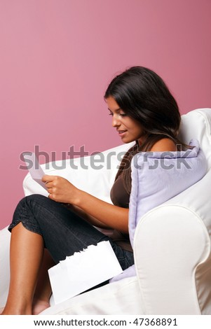 Women sat in an armchair reading a letter, blank envelope to add your own text. - stock photo