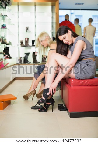 Women searching for shoes in a shop - stock photo