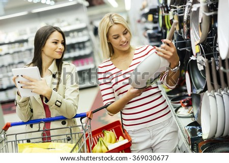 Women shopping cookware in supermarket - stock photo