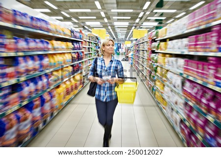 Women shopping in supermarket with basket - stock photo