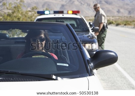 Women sitting in car being pulled over by police officer - stock photo