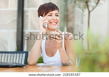 women sitting in garden cafe, talking on the phone and enjoying in beautiful day and her coffee - stock photo