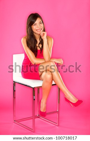 Women sitting portrait on pink. Woman sitting on chair in full length studio portrait on pink background. Beautiful smiling happy Asian Chinese / Caucasian. - stock photo