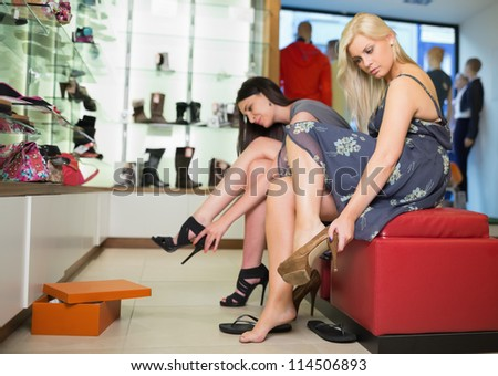 Women sitting trying on shoes - stock photo