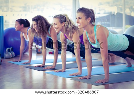 Women smiling while doing plank pose on exercise mat in fitness center - stock photo