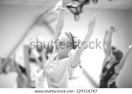 Women stretching hands up in fitness class, monochrome - stock photo