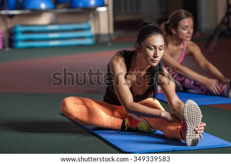 Women stretching legs on the floor in the gym - stock photo