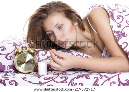 Women suffering from illness or insomnia lying in bed about to take a tablet and a displayed bottle of medication - stock photo