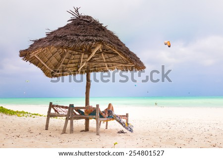 Women sunbathing on dack chair under wooden umbrella on stunning tropical beach. Kiteboarders turquoise blue lagoon of Paje beach, Zanzibar, Tanzania in the background. - stock photo