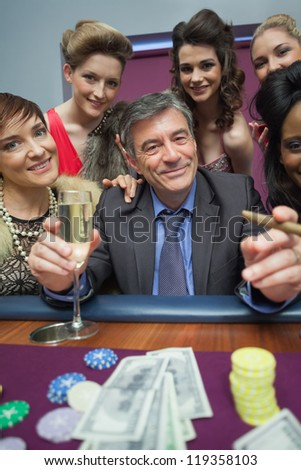 Women surrounding man at roulette table in casino - stock photo