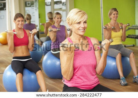 Women Taking Part In Gym Fitness Class - stock photo