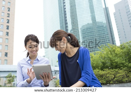 Women talk while having a tablet - stock photo