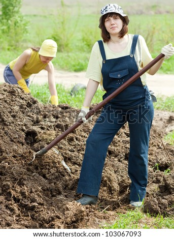 women throws the manure pitchfork in the field - stock photo
