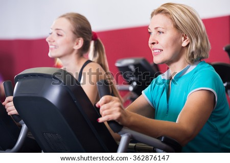 Women  training on exercise bikes in gym together - stock photo