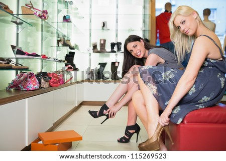 Women trying shoes on  smiling in shoe shop - stock photo