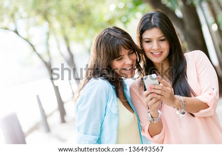 Women using a smart phone outdoors looking very happy - stock photo