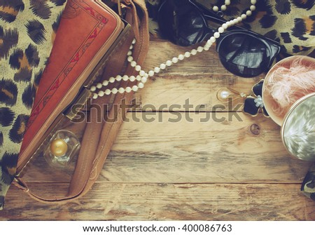 women vintage accessories, powder box, scarf, necklace, perfume, sunglasses and handbag on wooden table - stock photo