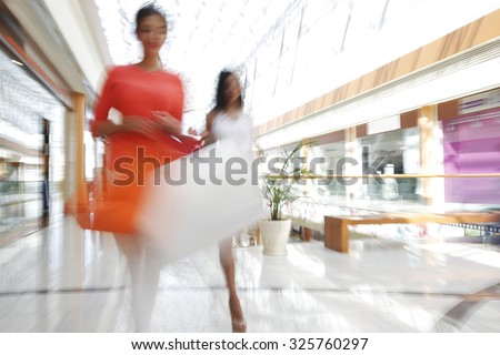 Women walking fast in shopping mall with bags - stock photo