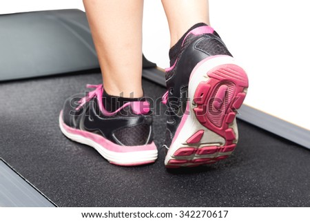 Women walking on treadmill on pink black sport shoes - stock photo