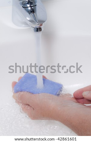 Women washes with running water and soap hands. Protection against the new flu infection. - stock photo
