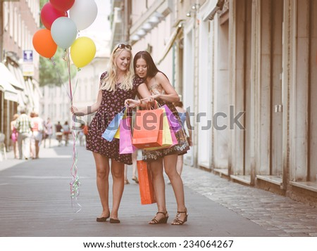 women watching at the time after long shopping. concept about shopping and leisure - stock photo