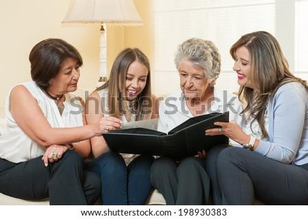 Women watching family album at home - stock photo