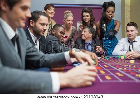 Women watching men play roulette in casino - stock photo