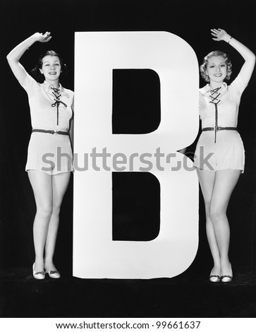 Women waving with huge letter B - stock photo