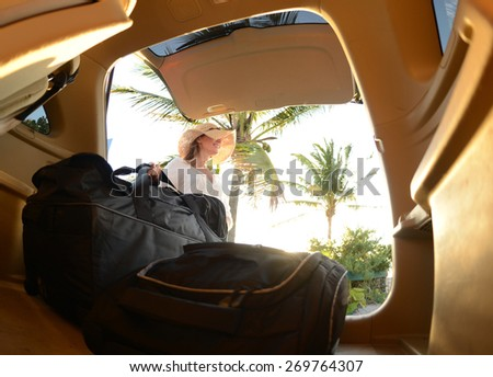 women wearing a hat on a tropical road trip with suitcases - stock photo