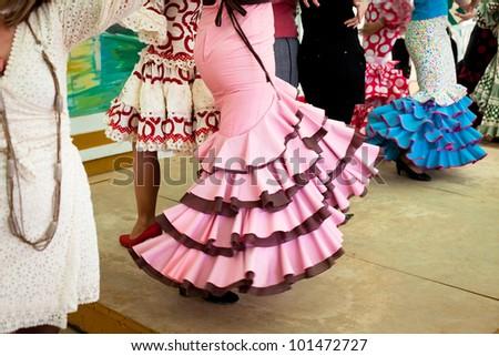 Women wearing flamenco dresses dancing sevillanas at Seville's Feria de Abril. - stock photo