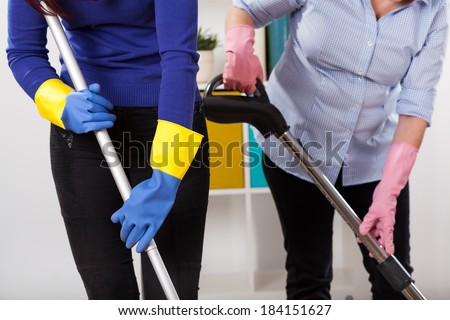 Women wearing protective gloves during cleaning floor - stock photo